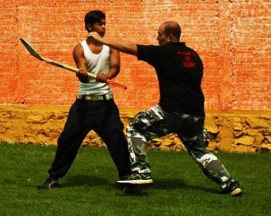 Krav Maga technique: instructor demonstrates defense against stick-like weapons