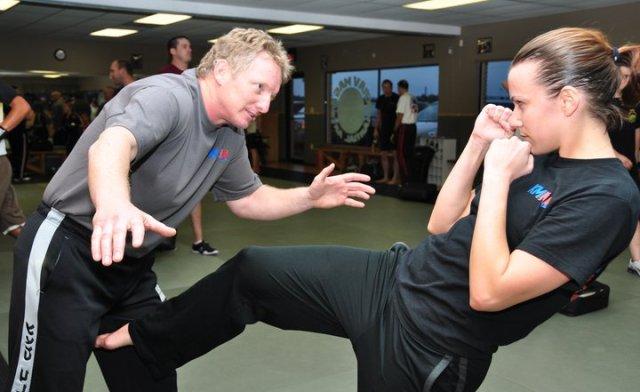 Krav Maga: woman does a groin kick to male attacker.