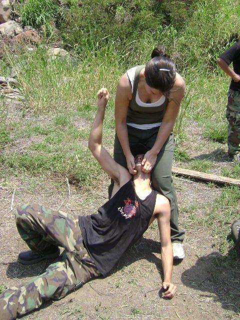 Krav Maga technique: women defender holds male attacker in tight choke grab by neck