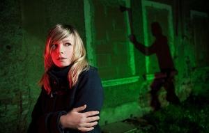 Woman looks frightened in dark alley